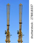 Two construction tower cranes isolated on blue sky background, synchronously parallel standing yellow objects