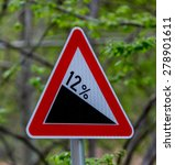 Small photo of Triangle red road sign showing 12% inclination. Forest green background.