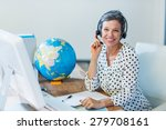 Small photo of Smiling travel agent sitting at her desk in the office
