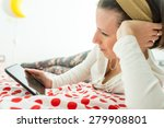 Small photo of Young woman wearing a golden alice band in her hair looking on digital tablet or e-book device lying on her bed on a red and white polka dot bedspread.