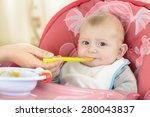 baby boy eating in a high chair ...   Shutterstock . vector #280043837