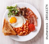 Small photo of English breakfast: fried egg, bacon, beans and toast on a plate close-up. horizontal view from above