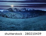 composite summer landscape with 3D mountains. village on agricultural meadow hillside in front of a high rocky mountain range at night in full moon light - stock photo