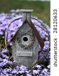 Weathered birdhouse in a bed of creeping phlox with shallow DOF - stock photo