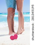 Small photo of Barefoot female legs standing up tiptoe on man's foots on beach with turquoise sea background, decorated pink heart object. Romantic honeymoon vacation concept