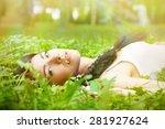 sad girl lying on green grass | Shutterstock . vector #281927624