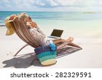 Productive businesswoman working on the beach - stock photo
