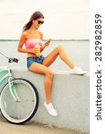 Small photo of Spending carefree time outdoors. Beautiful young smiling woman in headphones sitting on parapet near her bicycle and listening to the music