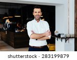 Small photo of Successful restaurant manager standing with crossed arms