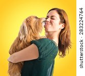 Stock photo girl hugging her dog over colorful background 283224764