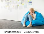 Small photo of Smiling businesswoman using mobile phone on beanbag chair in creative office