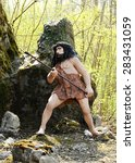 Small photo of April 10, 2015 Prehistoric Park, Rivolta D' adda, Lombardy, Italy : Statue of a Homo Sapiens Leaning on the Boulder and Holding a Primitive Weapon Hunting Tool, Emphasizing Hunting an Animal.
