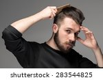 young man comb his hair on gray ... | Shutterstock . vector #283544825
