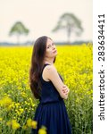 Profile of young beautiful woman with dark blue sleeveless dress and long dark hair standing on yellow blooming rapeseed field with crossed arms - stock photo