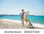 Stock photo beautiful girl in a blue blouse and shorts playing with dogs on the beach 283637264
