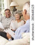 Small photo of Retired Senior Couple Sitting On Sofa Talking To Financial Advisor