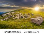 composite landscape with white sharp boulders on the hillside near mountain peak in evening light - stock photo