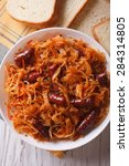 Small photo of braised sauerkraut with sausages close-up in white plate. vertical top view