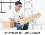 Small photo of Indian guy received an express parcel and checking the box at home. Handsome male portrait. Asian man sitting on sofa indoor. Courier delivery concept.