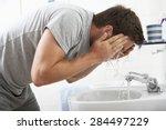 Man Washing Face In Bathroom...