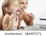 Mother And Daughter Brushing...