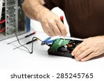 Small photo of man is repairing computer hardware on a desk