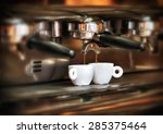 Italian espresso machine on a counter in a restaurant dispensing freshly brewed coffee into two small cups to be served to customers - stock photo