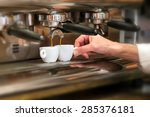 Close up view of the hand of a man working in a coffee house preparing espresso coffee waiting for the coffee machine to finish pouring the fresh beverage into two small cups - stock photo