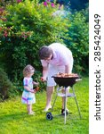 Father And Child Grilling Meat...