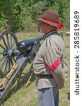 Small photo of HUNTERSVILLE, NC - JUNE 6, 2015: A reenactor in a Confederate army uniform stands next to a 10-pound Parrott gun during an American Civil War battle reenactment at Historic Latta Plantation.