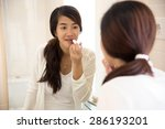 A portrait of a Beautiful asian woman putting make-up on, applying lipstick on her lips