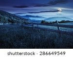 rural landscape. fence on the hillside meadow shot with ultrawideangle lense. forest in fog on the mountain top at night in full moon light - stock photo