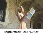 Small photo of Portrait of young female tourist checking out the sights while reading a map, gorgeous woman holding a map while touring abroad,stylish hipster studying a map while standing in antique town in summer