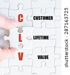 Small photo of Hand of a business man completing the puzzle with the last missing piece.Concept image of Business Acronym CLV as Customer Lifetime Value