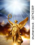 gold angel with rays of divine light over beautiful sky - stock photo