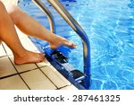 Female Legs In The Pool Water