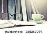 Glasses On Open Book With Cup...