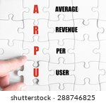 Small photo of Hand of a business man completing the puzzle with the last missing piece.Concept image of Business Acronym ARPU as Average Revenue Per User