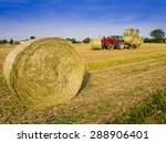 tractor collecting hay bales in ...