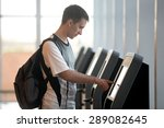 Small photo of Young man with backpack touching interactive display at self-service transfer machine, doing self-check-in for flight or buying airplane tickets at automatic device in modern airport terminal building