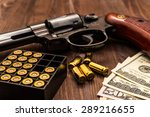 Small photo of Revolver with cartridges and money on the wooden table