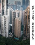 Aerial view of crowded Hong Kong high rises meeting the edge of the forest on Victoria Peak - stock photo