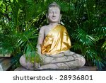 Statue of Buddha meditating in a lush green garden - stock photo