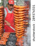 Small photo of KUALA LUMPUR, MALAYSIA : JUNE 20, 2015 - A hawker tends to his stall selling chicken wings at a ramadhan bazaar