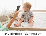 happy mother using her phone... | Shutterstock . vector #289406699