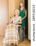 Small photo of Smiling old woman in wheelchair with young assistant at threshold