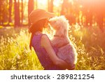 Stock photo young girl holding her dog rural sunny landscape 289821254
