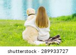 Stock photo silhouette of owner and golden retriever dog sitting together on the grass near river in sunny 289933727