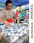 Small photo of KUALA LUMPUR, MALAYSIA : 20 JUNE, 2015 - A hawker selling putu piring kuih pastry at a ramadhan bazaar in Kuala Lumpur.