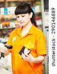 Small photo of seller cashier with bar code scanner scanning lamp at store